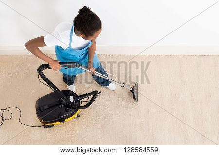 High Angle View Of Young Female Janitor Cleaning Floor With Vacuum Cleaner