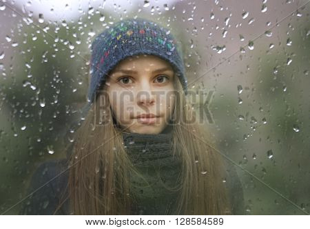 A portrait of a young girl looking through a window with raindrops