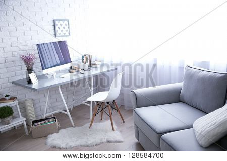 Modern interior. Comfortable workplace. Wooden table with beautiful bouquet of flowers and computer on it.