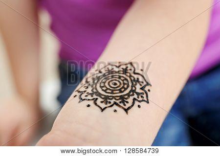 Image of henna ornament on girl's wrist closeup