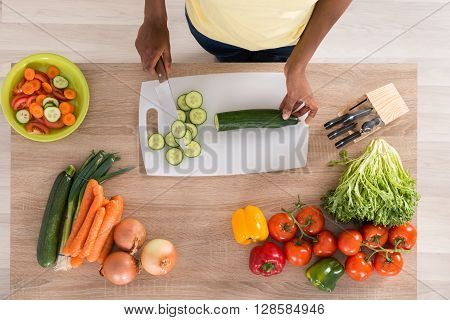 High Angle View Of Young African Woman Chopping Vegetables On Chopping Board