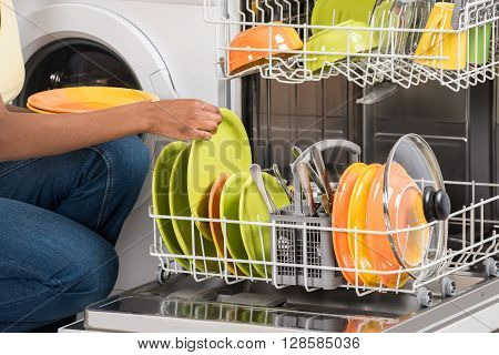 Close-up Of Woman's Hand Arranging Plates In Dishwasher At Home
