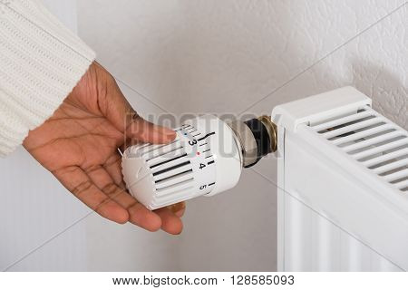 Close-up Of Person's Hand Adjusting Radiator Temperature