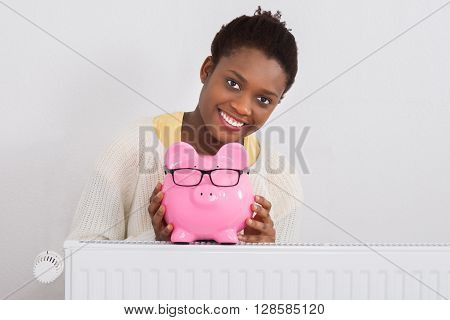 Young African Woman Leaning On Radiator With Pink Piggybank At Home