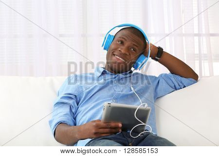 Handsome African American man with headphones and tablet sitting on sofa close up