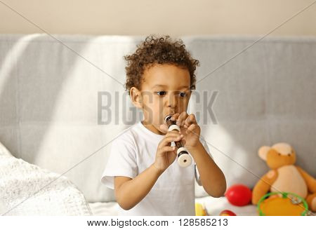 Little boy playing on recorder