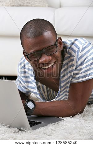 Handsome African American man lying with laptop on carpet in room