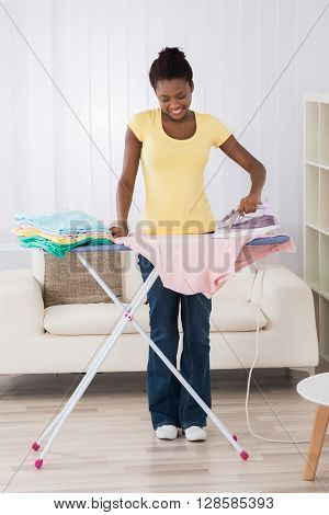 Young Happy African Woman Ironing Clothes On Iron Board At Home