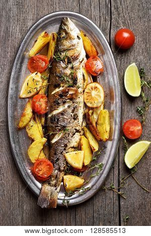 Roasted fish with potato wedges on wooden background top view