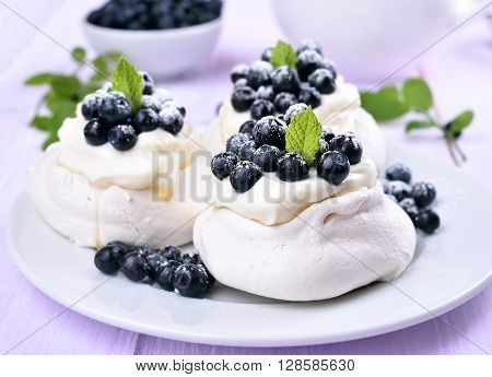 Pavlova meringue cakes with fresh blueberries on plate