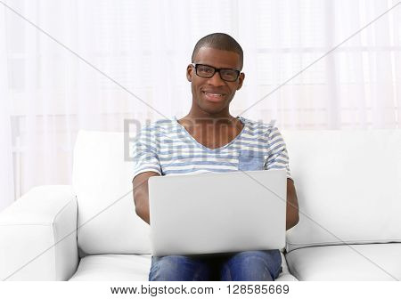 Handsome African American man sitting with laptop on sofa in room