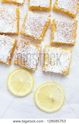 Lemon bars and slices over baking paper top view