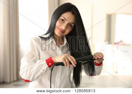 Beautiful woman with hair iron