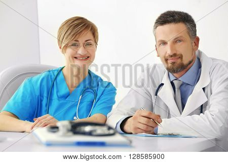 Male and female doctors sitting at the table in the hospital, indoors