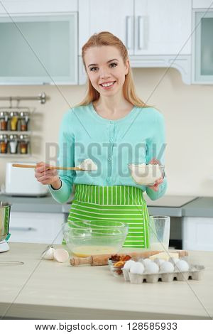 Young woman adding a flour to make a dough