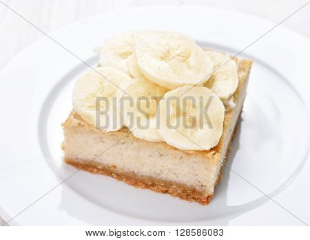 Banana cheese cake on white plate close up view