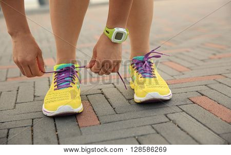 young woman runner tying shoelace at seaside