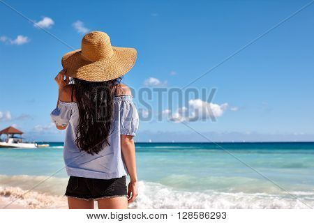 Beach vacation. A beautiful woman in a sunhat standing on beach and watching the emerald water of the ocean