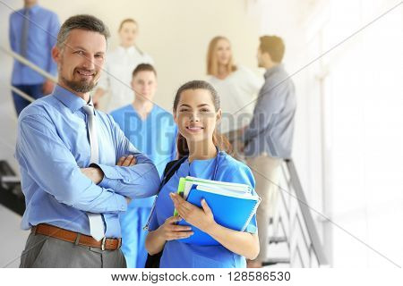 Young female medical student and professor standing indoors