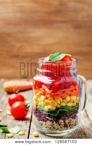 homemade rainbow salad with vegetables and quinoa on a dark wood background