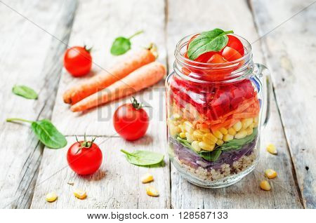 homemade rainbow salad with vegetables and quinoa on a white wood background