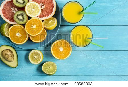 ripe juicy citrus fruit juice ice on a blue wooden table top view