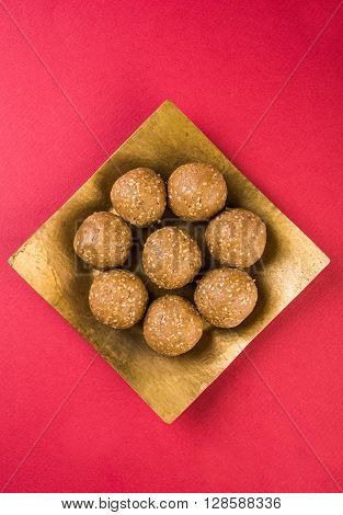 The indian sesame sweet or tilgul laddu, made up of jaggery and sesame seeds, hand made, round, indian sweet prepared in Makar Sankranti festival, served in a square brass plate, top and isolated