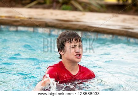 Handsome and silly teen boy with braces making mouth puckered in swimming pool