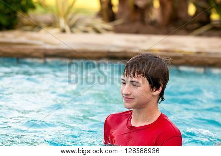 Handsome and happy teenage boy standing in pool with copy-space.
