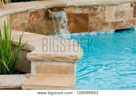 Beautiful swimming pool with flagstone wall that has waterfall pouring out of it.