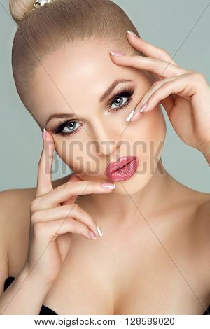 Spa, beauty, skin care, fitness and health. Glamour closeup portrait of beautiful female model face with healthy clean skin and Golden makeup and a French manicure. The Studio, grey background