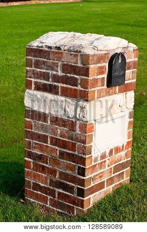 Red brick and white stone mailbox with green grass in background.