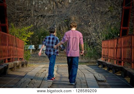 Two boys from behind walking on an old bridge.