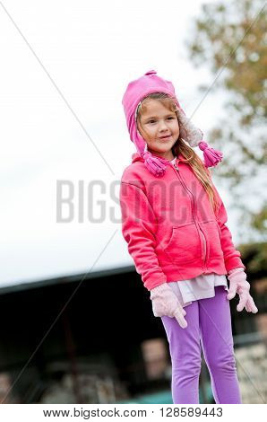 Happy Little girl bundled in pink winter clothes on a windy day.