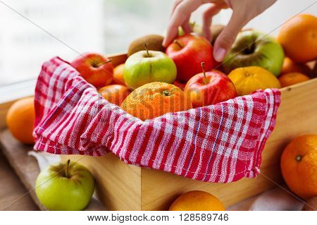 Box full of fresh fruits. Woman chooses fruits. Fruit harvest - apples oranges lemon kiwi banana. Rustic background.