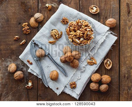 Glass bowl with walnuts on rustic homespun napkin. Healthy snack on old wooden background.