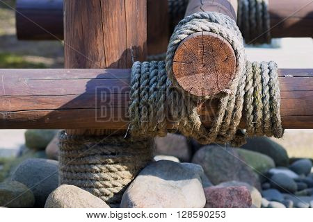 closeup a design fragment from wooden logs is fastened by a rope