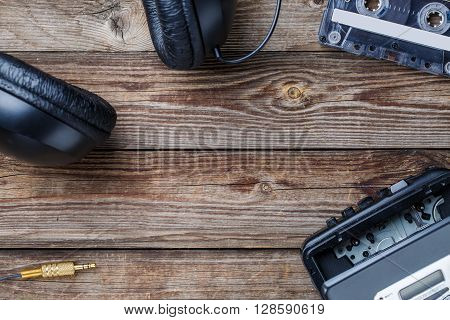 Cassette tapes, cassette player and headphones over wooden table. top view. Retro concept with empty space for text, logo, etc.