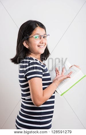 indian small girl with eye glasses standing and reading a book, asian little girl holding a book and reading over white background, cute indian girl wearing spectacles and reading book while standing