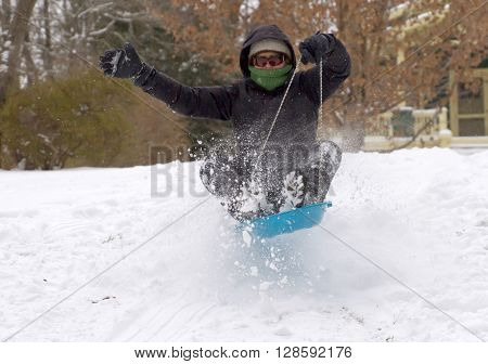 Asheville; North Carolina; USA - January 23 2016: A bundled up young woman sleds down a hill over a bump in a wild and airborne spray of snow on a cold winter's day