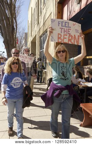 Asheville North Carolina USA - February 28 2016: A crowd of Bernie Sanders rally supporters march holding a variety of signs about isues like health care during a campaign rally on February 28 2016 in downtown Asheville NC