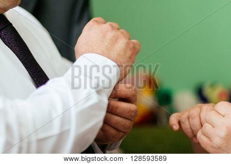 Hands of the groom dressing groom hands