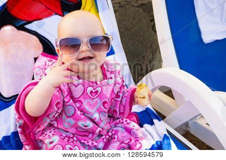 Happy baby girl in sunglasses on holidays at the pool