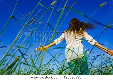 Young woman walk on green field