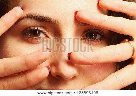 Woman peeking behind her hand (close up)