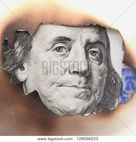 burning dirty dollar bill as a symbol of inflation and the financial crisis