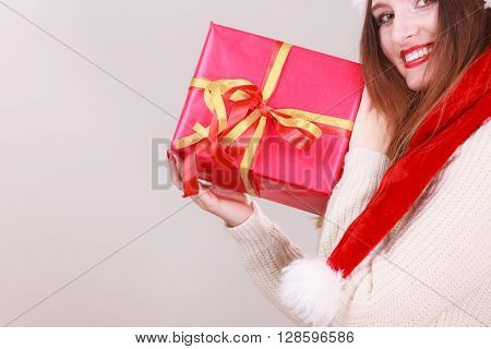 Happy girl holding gift. Young woman in santa cap with ribbon box. Holiday celebration relax lifestyle leisure concept.