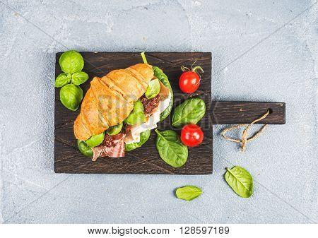 Croissant sandwich with smoked meat Prosciutto di Parma, sun dried tomatoes, fresh spinach and basil on dark wooden board over stone textured grey background, top view