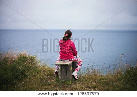 Young school girl resting on bench and enjoying look at ocean