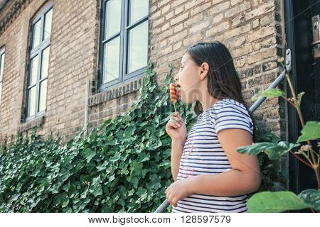 Girl eats ice-cream in front of house
